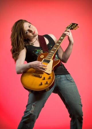 Rocker Girl Musician Guitar Player jamming on electric guitar on hot pink background Stock Photo