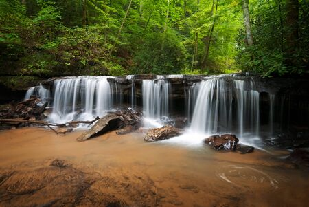 Peaceful Forest Waterfalls Landscape Flowing in Summer Stock Photo