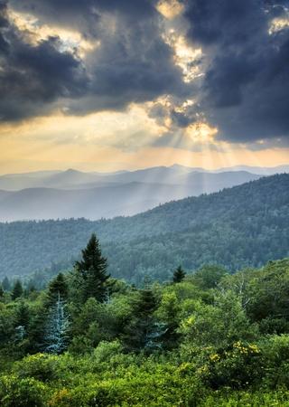 wnc: Sunbeams Light Rays Over Southern Appalachian Blue Ridge Mountains at dramatic summer sunset Stock Photo