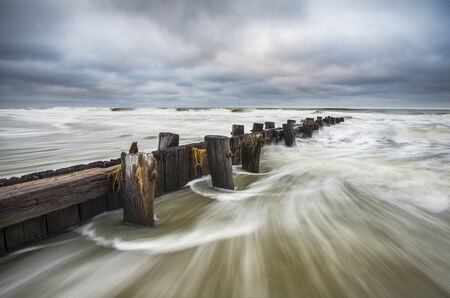 coastal erosion: Folly Beach South Carolina Charleston SC Seascape landscape photography featuring moving ocean water against an old wooden erosion control breakwater Stock Photo