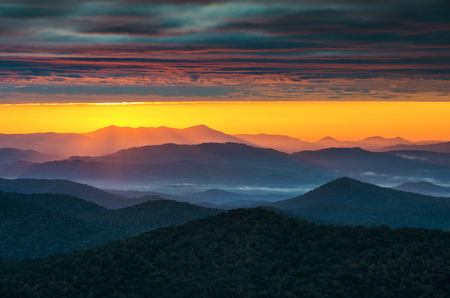North Carolina Blue Ridge Parkway Sunrise near Asheville NC featuring crepuscular light rays shining over endless Appalachian mountain ridges