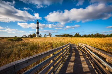 A sunny morning just after sunrise at Bodie Island Lighthouse near Nag's Head on the Outer Banks of North Carolina. The first iconic symbol along the Cape Hatteras National Seashore most people see when arriving at OBX, many people see this iconic lighthouse as a