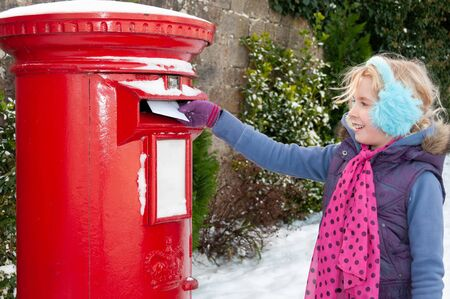 Young blonde girl in blue ear muffs posting her letter to Santa. Traditional British red Post Box partially covered in snow. Stock Photo