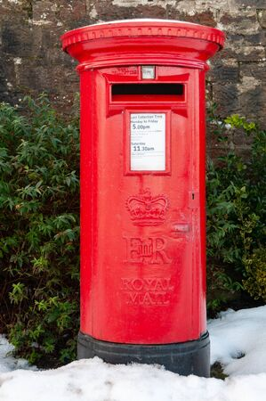 A traditional red British Post Box in a snowy rural setting. An old fashioned pillar box with snow on the ground. Stok Fotoğraf