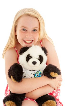 Close up of very happy beautiful young blonde girl with a big smile cuddling her teddy bear and making eye contact. Isolated on white studio background Imagens