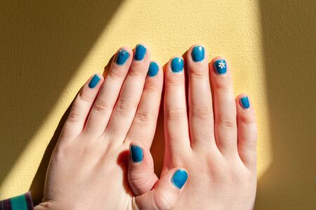 Vibrantly painted blue fingernails in a line with interlocking thumbs