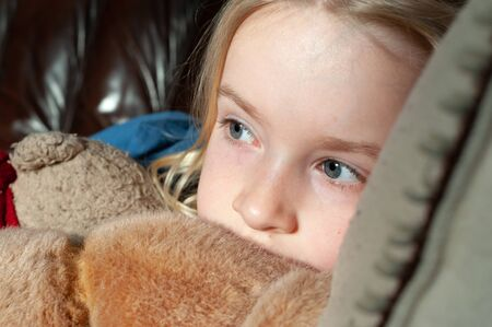 Close up of pretty young blonde girl's eyes while cuddling her teddy