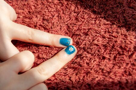 Two blue painted fingernails with flower and eye details Banque d'images