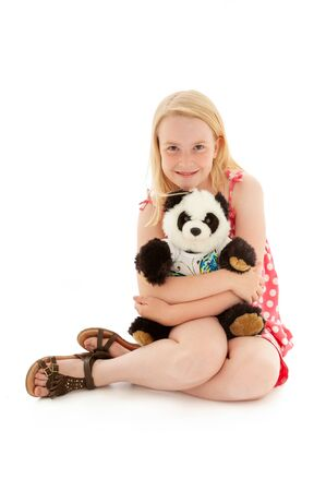 Beautiful young blonde girl cuddling her teddy bear and making eye contact. Isolated on white studio background Stock Photo