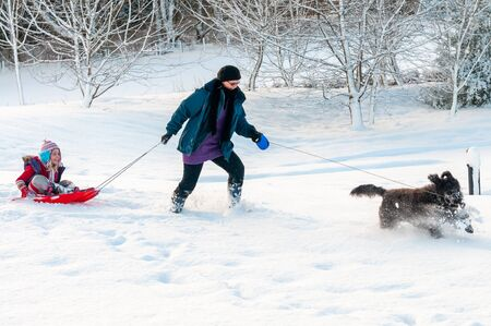 Black dog leading mother with daughter sledging behind through deep snow in a rural setting Stock Photo
