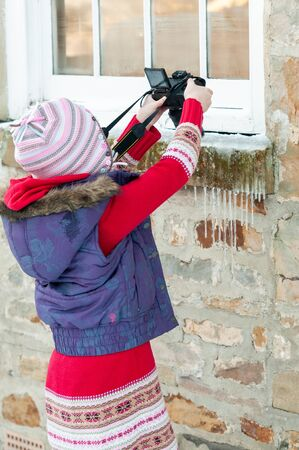 Young girl taking an overhead photograph of icicles hanging from a stone window ledge Stock fotó