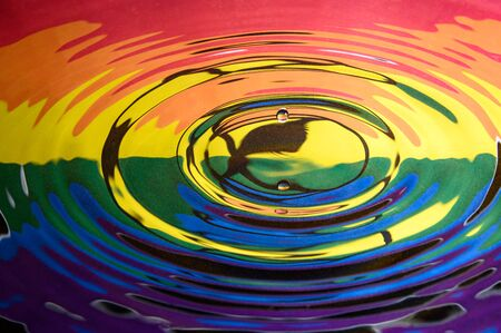 A falling water drop reflected in the circular waves from a splash and the colours and logo of Extinction Rebellion. Abstract Extinction Rebellion climate change background.