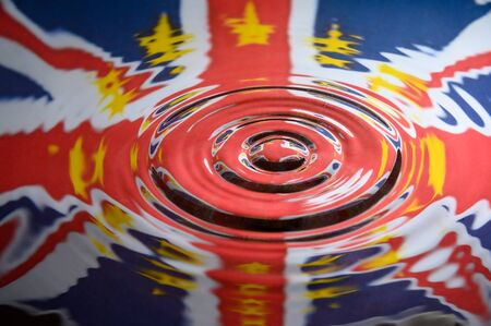 UK Union Jack with the Stars of the European Union reflected in the ripples of a water splash. Abstract Brexit background.