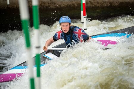 Close up action of a GB Canoe Slalom Athlete negotiating the poles of slalom gates on white water in the C1W class.