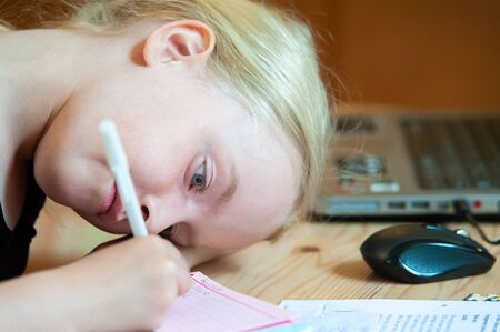 Young blonde girl with head down low writing. Laptop and mouse out of focus in the background
