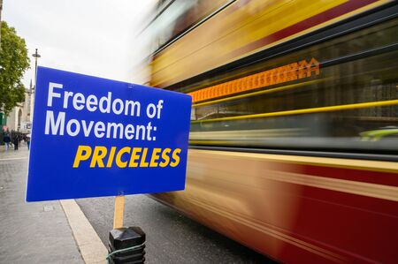 Red and gold London bus with motion blur as it passes anti-Brexit Freedom of Movement sign