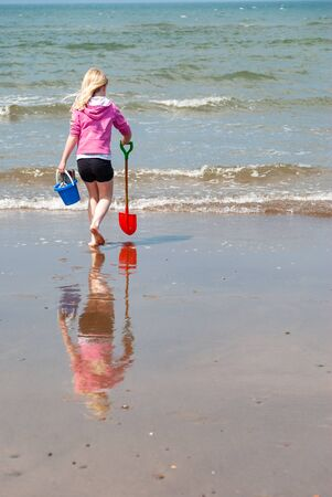 A young girl carries a bucket and spade to the shoreline on a beach. Her reflection is visible in the wet sand.