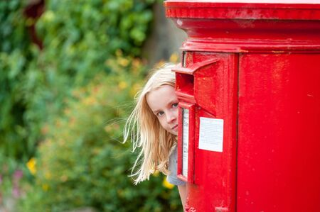 A young blonde girl peeks around a traditional red British Post Box. 版權商用圖片