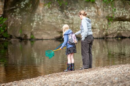 A mother and daughter with fishing nets at the edge of a river. Stock Photo