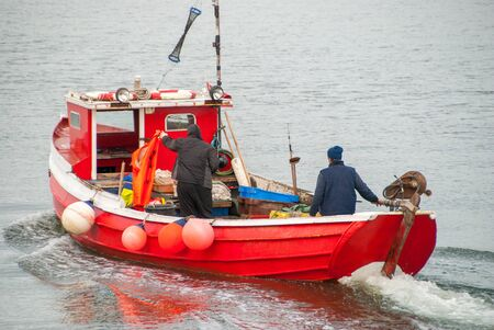 Two fishermen aboard a moving small red fishing boat.