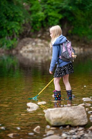 A young blonde girl with backpack and fishing net wades in the shallow water of a river while wearing wellies