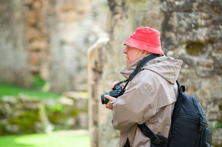 An elderly man with a camera in ancient ruins.
