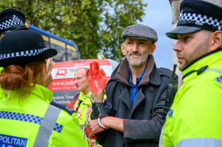 LONDON - OCTOBER 18, 2019: Handcuffed male Extinction Rebellion protester with red painted hand surrounded by Police Officers Editorial