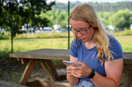 Close up of a young blonde female adult sat at an outdoor picnic table using a smartphone.