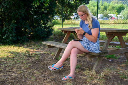 Young blonde female adult sat at an outdoor picnic table using a smartphone.