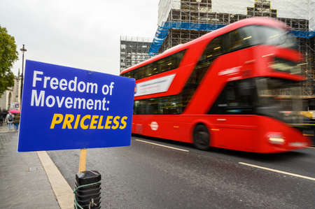 Red London Double Decker bus with motion blur passes anti-Brexit Freedom of Movement sign outside The House of Parliament