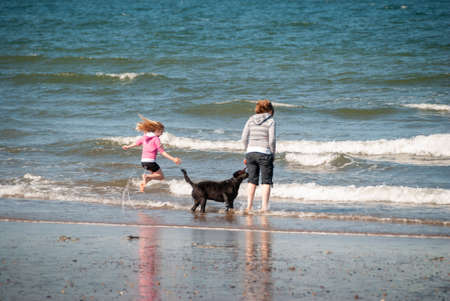 A mother and daughter with a black dog jump over the breaking waves on a beach.