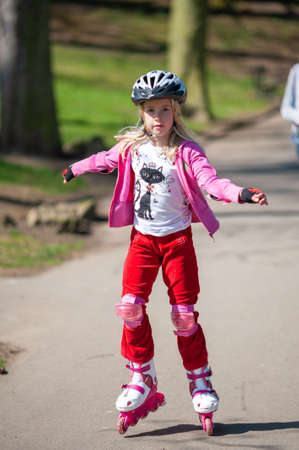 A young girl on roller blades wearing protective equipment