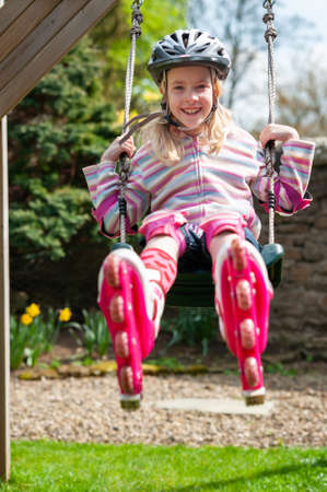 A smiling young blonde girl wearing roller blades and helmet while swinging on garden swing. Stock fotó