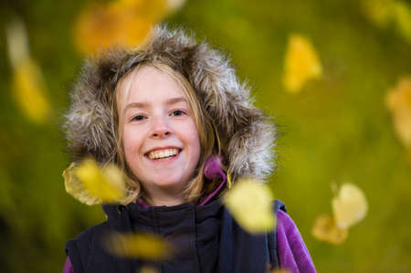 Beautiful happy young girl in a fur lined hood and surrounded by falling leaves.