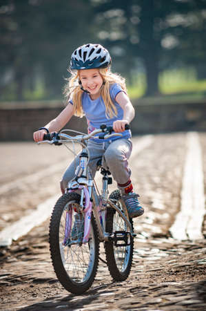 A very happy young blonde girl rides a bike along a cobbled path towards camera in golden sunlight