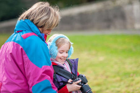 Happy young girl holding a camera and wearing blue ear muffs shows camera to mother.