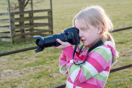 Young blonde girl using a camera with a large zoom lens. Back lit by setting golden sun.