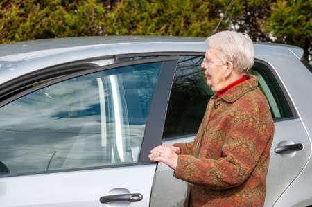 An elderly lady opening a car door.