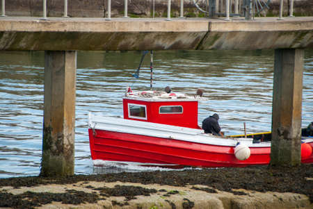 A small red fishing boat between the posts of a pier on a calm day. Stock fotó