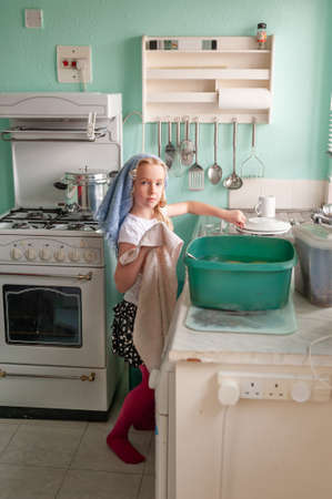 Young girl drying dishes at a kitchen sink. Stock fotó