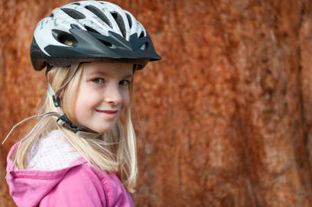 A young blonde girl poses in a cycle helmet Stock fotó
