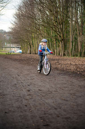A young girl riding a bike along a country track towards the camera.