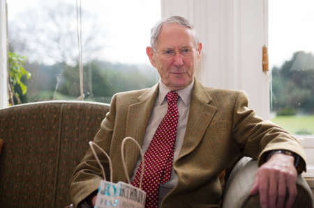 A well dressed elderly man sat in front of a bright window.