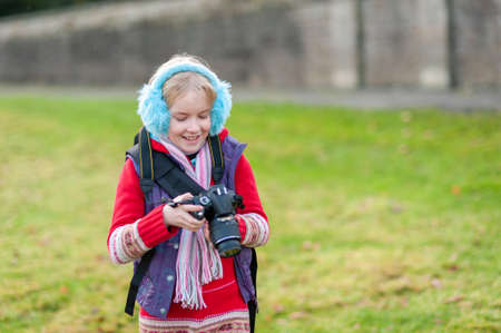 Happy young girl holding a camera and wearing blue ear muffs.
