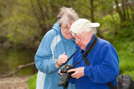 Elderly couple review photographs on the back of a DSLR camera. Stock fotó