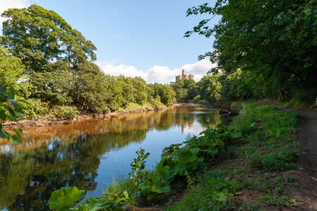 View of rowing boats along the River Coquet and the path towards Warkworth Castle on a sunny day.