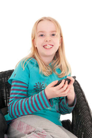 Close up of a happy young blonde girl sat on a wicker chair holding a smartphone. Isolated on white studio background