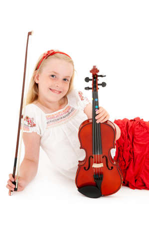 Smiling young blonde girl poses with violin on a white studio background. Foto de archivo