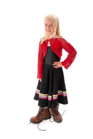 Smiling young blonde girl dressing up in Dad's big walking boots. Isolated on white background Foto de archivo