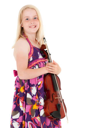 Smiling young blonde girl in a flowery dress poses with violin on a white studio background. Foto de archivo